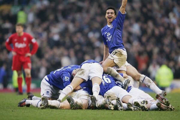LIVERPOOL, ENGLAND - DECEMBER 11: Tim Cahill of Everton celebrates as the Everton tean pile on top of goal scorer Lee Carsley during the Barclays Premiership match between Everton and Liverpool at Goodison Park, on December 11, 2004 in Liverpool, England