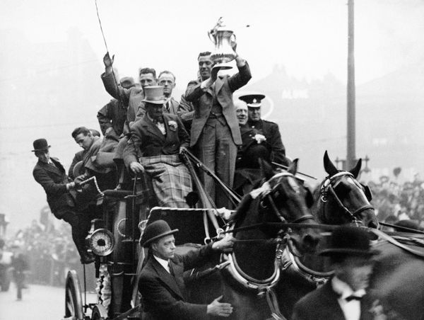 Everton's Bill 'Dixie' Dean holds up the FA Cup as the team emerge onto Lime Street, Liverpool