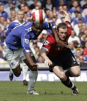 Everton's Yobo challenges Manchester United's Rooney for the ball during