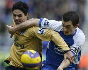 Wigan Athletic's Baines challenges Everton's Arteta for the ball during their