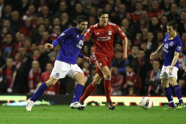 Liverpool's Martin Kelly (centre) and Everton's Denis Stracqualursi (left) battle for the ball