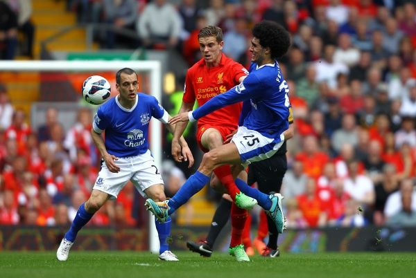 Liverpool's Jordan Henderson and Everton's Marouane Fellaini (right) battle for the ball