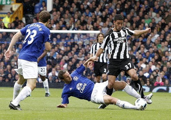 Everton's Phil Jagielka (centre) challenge's Newcastle United's Hatem Ben Arfa (right) for the ball